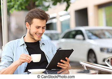 Man reading an ebook or tablet in a coffee shop - Happy man...