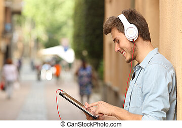 Man using a tablet with headphones on the street - Profile...