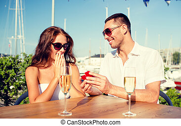 smiling couple with champagne and gift at cafe - love,...