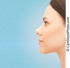 beautiful young woman face over blue background - health,...