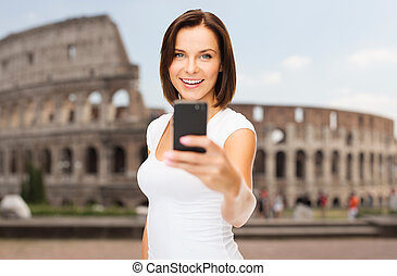 woman taking selfie with smartphone over coliseum - people,...