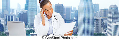 female doctor with laptop reading medical report - health...