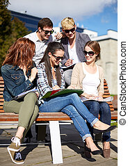 group of happy students with notebooks at campus - summer,...