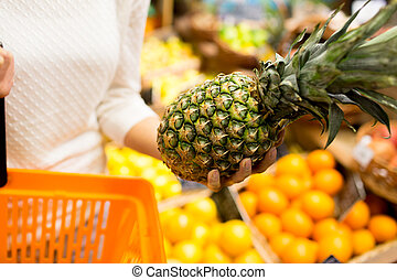 close up of woman with pineapple in grocery market - sale,...