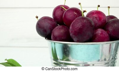 Plums in small metal bucket on the wooden table.