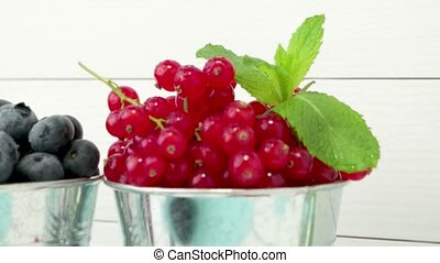 Red currants in small metal bucket on the wooden table.