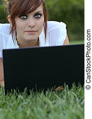 Pretty young woman lying on the grass - using her laptop computer