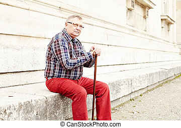 Man with stick sitting outdoor - Portrait of mature man in...