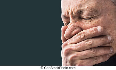 Toothache.  Elderly man with face closed by hand