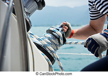 Winch and sailors hands on a sailboat. Shot with a selective...