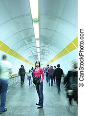 Subway - young woman standing in a subway corridor while the...