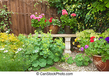 Colorful potted plants in garden corner with a stone bench....