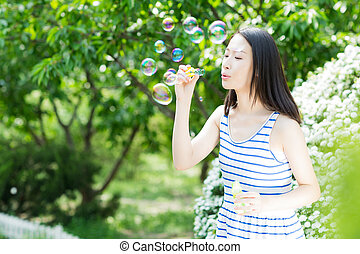 the park beautiful girl - blowing bubbles in the park young...
