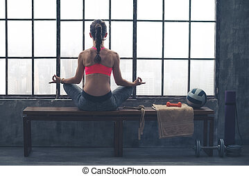 Rear view of woman on bench in lotus position in loft gym -...