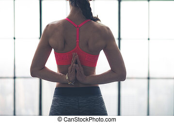 Rear view of womans hands clasped behind back in yoga pose -...