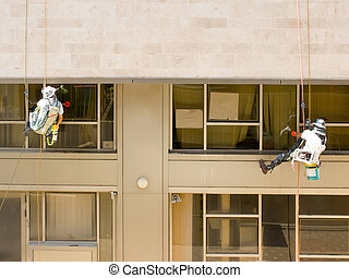 Window washers - Two professional workers washing windows on...