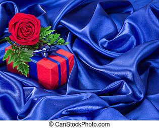 Gift with rose on silk fabric - Red gift box with blue bow...