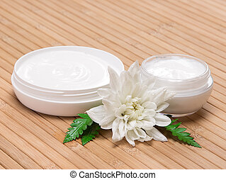 Open jars of cream with white flower and fern leaves -...