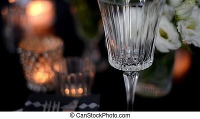 Luxurious festive table setting with candles, flowers,...
