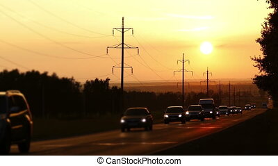 string of cars moving on road against sunset