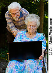 Elderly couple having fun with the laptop outdoors