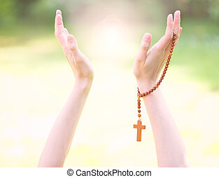 Hands holding wooden rosary
