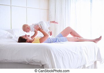 Mother and baby relaxing in white bedroom - Mother and baby...