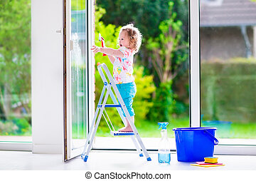 Little girl washing a window. Kids clean the house. Children...