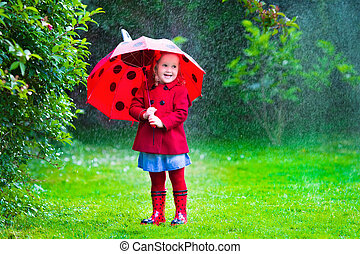 Little girl with umbrella playing in the rain - Little girl...
