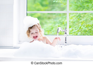 Baby girl taking bath with foam - Child taking bath. Little...