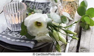 Table setting with white flowers, candles and glasses on old...
