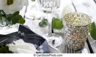 Champagne pouring into a glass. Table setting with white...