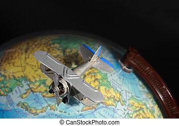 Airplane On Globe - Miniature model of vintage biplane on...