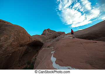 Woman walking on a slickrock Cave Point Escalante Utah...