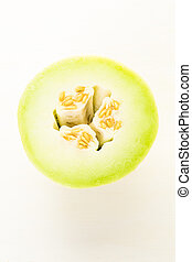 Honeydew - Organic honeydew melon sliced on white wood board...