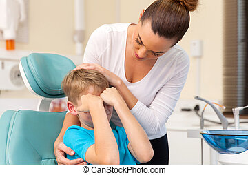mother comforting her son in dentist office - caring mother...