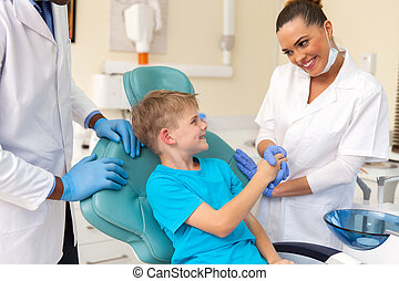 female dental assistant greeting little patient