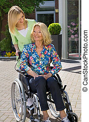 Nurse with Senior Woman in Wheelchair Outdoors - Blond Nurse...