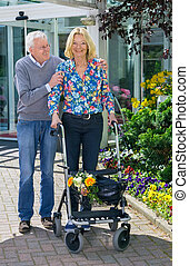 Senior Man Helping Woman with Walker Outdoors