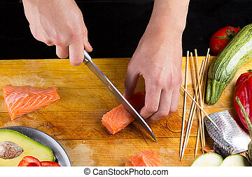 chef is slicing salmon filett on a wooden board