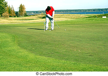 Golfer - A golf club (driver) about to strike a golf ball on...