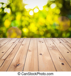 Empty wooden deck table with foliage bokeh background. Ready...
