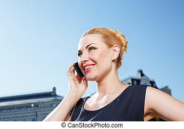Busy woman talking per mobile phone outdoor - Sincere smile....