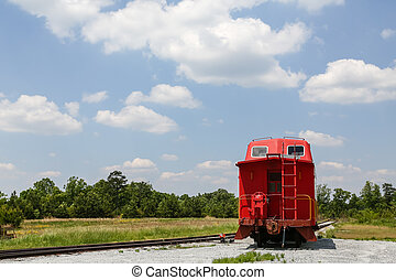 Caboose Beside Tracks - An old red caboose on a track under...