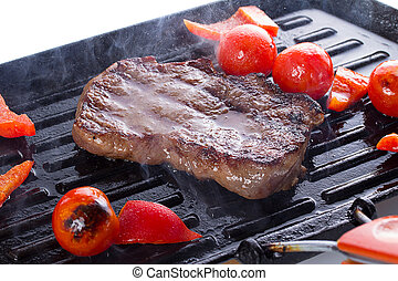 Stake with cherry tomato on a hot grill