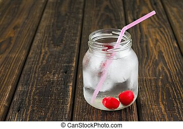 Two cherries in cold drink in a jar with pink straw -...