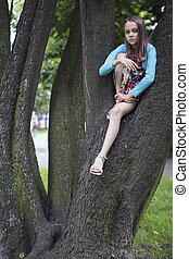 cute girl sitting on the branches