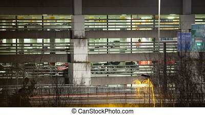 Timelapse of traffic near parking deck at night - Timelapse...