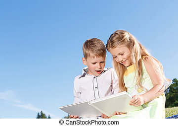 Cute smiling boy and girl reading book