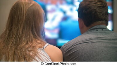 Young man and woman watching television at home
